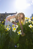 Girl finding chocolate Easter eggs in flowers Royalty Free Stock Images