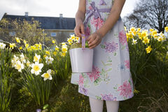 Girl finding chocolate Easter eggs in flowers Stock Images