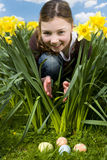 Girl finding easter eggs in grass Royalty Free Stock Photos