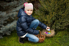Girl finding Easter eggs on lawn at backyard Stock Image
