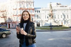 Girl finding her way in city. Portrait of charming caucasian female in trendy outfit walking on street, smiling at Stock Images