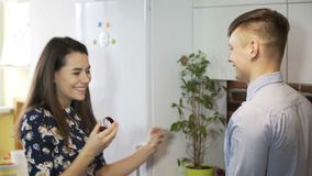Girl finding ring box in refrigerator. Making surprise marriage proposal at home. The guy makes a marriage proposal to his girlfriend at home stock video footage