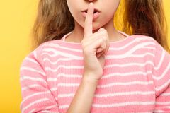 Smiling girl finger lips naughty secret conspiracy. Girl with finger on lips. naughty child secret and conspiracy. cropped shot royalty free stock photo