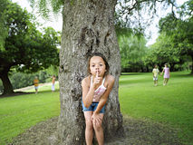 Girl (7-9) with finger on lips playing hide and seek in park, hiding from friends behind tree Stock Images