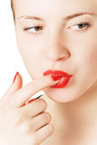Girl with a finger in mouth Stock Photos