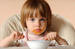 Girl finished eating spaghetti sitting on the chair Royalty Free Stock Photography