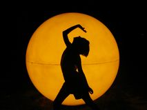 Girl on fire. Girl in front of an orange ball Stock Photos
