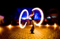 Girl with fire, blurred motion. Defocused crowd on background Stock Photos