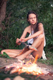 The girl at a fire in tropics. The beautiful girl in tropics sits at a fire Royalty Free Stock Photo