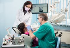 Girl with on the first dental visit. Senior pediatric dentist with nurse treating patient teeth at the dental office. Young girl with on the first dental visit Royalty Free Stock Images