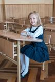 Girl in the first grade, is sitting at the desk. First grade student at school at the desk. emotions of schoolgirls Stock Image