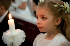 Girl at first holy communion. Side portrait of young girl with white dress at first holy communion looking at candle Stock Photo