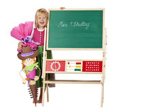 Girl on first school day stands beside chalk board Stock Photos