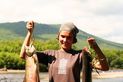 The  girl with the fish. On the river bank, Kamchatka Royalty Free Stock Photos