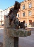 Girl and fish. Fountain and artistic figures Piotrowska Street Stock Photos