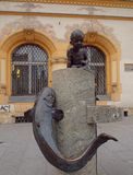 Girl, fish and house. The girl with a fish on a small fountain in the street Piotrowska in Lodz Stock Photography