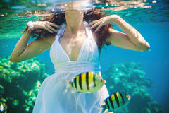 Girl with fish under the water Stock Photo
