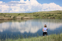 Girl Fishing. Girl standing at the edge of a pond fishing royalty free stock photo