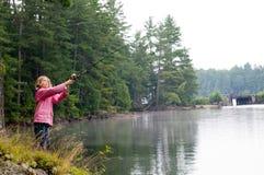 Girl fishing on the bank of a lake Stock Image