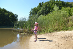 Girl fishing. Girl goes fishing with a fishing rod on nature, summer, Sunny, lake Royalty Free Stock Photography
