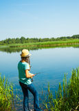 Girl while fishing by lakeside Royalty Free Stock Photos