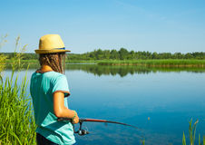 Girl while fishing by lakeside Stock Photo