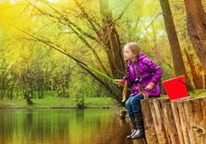 Girl fishing near beautiful pond with fishrod Royalty Free Stock Photo