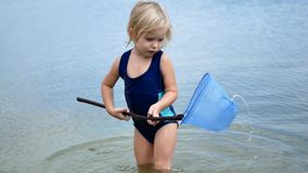 The girl is fishing the net. The child is played in the water stock video footage