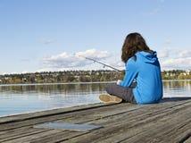 Girl fishing off Dock stock image