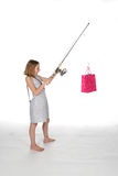 Girl with fishing pole and pink gift bag Stock Images