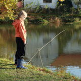 Girl fishing on pond Stock Photos