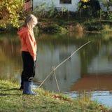 Girl fishing on pond stock photos
