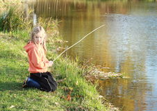 Girl fishing on pond Stock Image