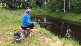 Girl fishing at pond and play with little cat. Free time nature Royalty Free Stock Image