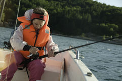 Girl with a fishing rod in a boat Stock Photography
