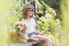Girl fishing while sitting with dog on pier royalty free stock images