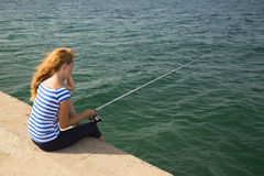 Girl fishing. Girl sitting with a fishing rod on the beach and fishing stock images