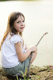 Girl fishing with a stick and line Royalty Free Stock Image