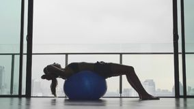 Girl with Fitness Ball. Silhouette of gorgeous girl with fitness or pilates ball in gym with view over cittyscape in slow motion stock video