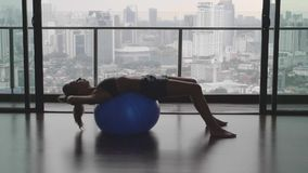Girl with Fitness Ball. Silhouette of gorgeous girl with fitness or pilates ball in gym with view over cittyscape in slow motion stock footage