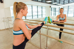 Girl in fitness class. Attractive sport girl smiling and looking in the mirror while stretching the body in fitness class Stock Photos