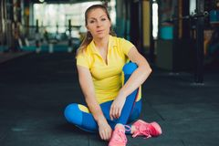 Girl in fitness club. Young woman athlete sitting on floor in the gym Stock Photos