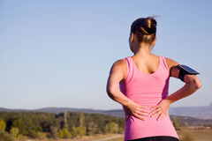 Girl after fitness feels pain in the back. Girl after fitness feels pain in his back on nature Royalty Free Stock Image