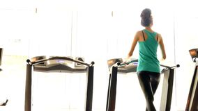 Girl in fitness hall. Girl is engaged in fitness club exercise on a treadmill stock footage