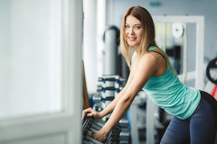Girl fitness trainer chooses dumbbells for training. Royalty Free Stock Images