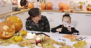 Girl fitting mask. Woman in glasses sitting at kitchen table and looking at her daughter fitting white mask for Halloween party stock video