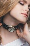 Girl fitting vintage watch on neck. Close-up portrait of blonde fashion girl fitting vintage watch on neck, studio shot Stock Photo