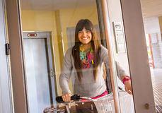 Girl with fixie bike opening a glass door to exit Stock Image