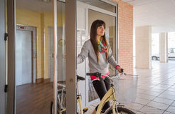 Girl with fixie bike opening a glass door to exit Stock Photography