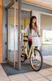 Girl with fixie bike opening a glass door to exit Royalty Free Stock Images